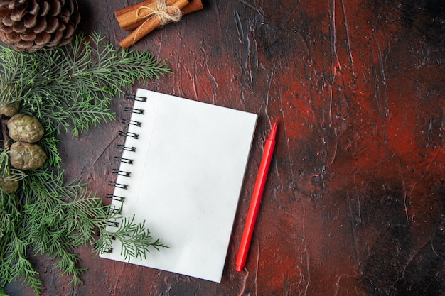 Nahaufnahme von tannenzweigen und geschlossenem spiralnotizbuch mit stift-zimt-limonen-koniferenkegel auf dunklem hintergrund