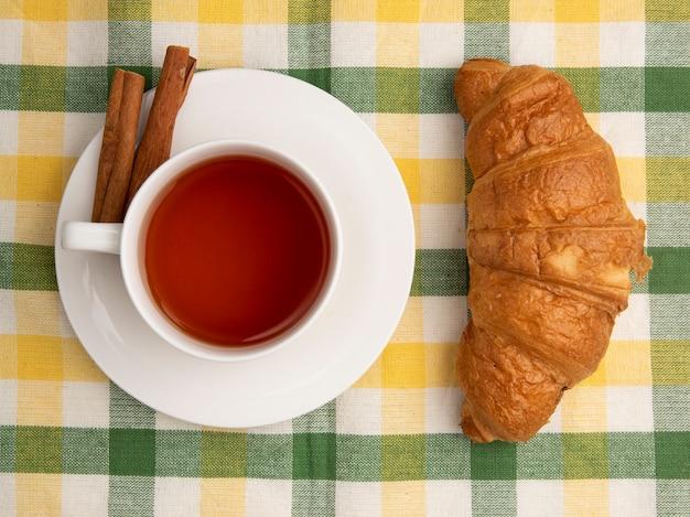 Nahaufnahme von tasse tee mit zimt auf teebeutel und japanischer butterrolle auf stoffhintergrund