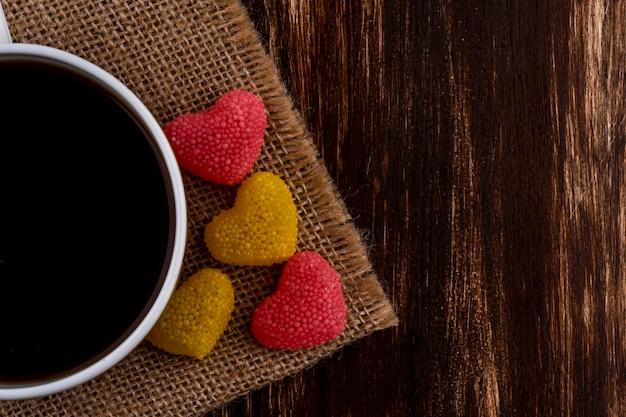 Nahaufnahme von tasse tee und marmelade auf sackleinen und hölzernem hintergrund mit kopienraum