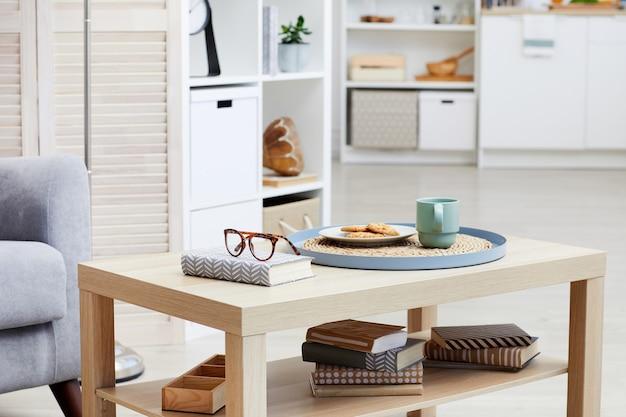 Nahaufnahme von tee mit keksen auf dem tablett sind auf holztisch im wohnzimmer im haus