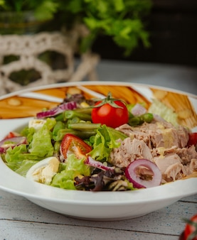 Nahaufnahme von thunfischsalat mit eiern, zwiebeln, salat, tomaten und erbsen