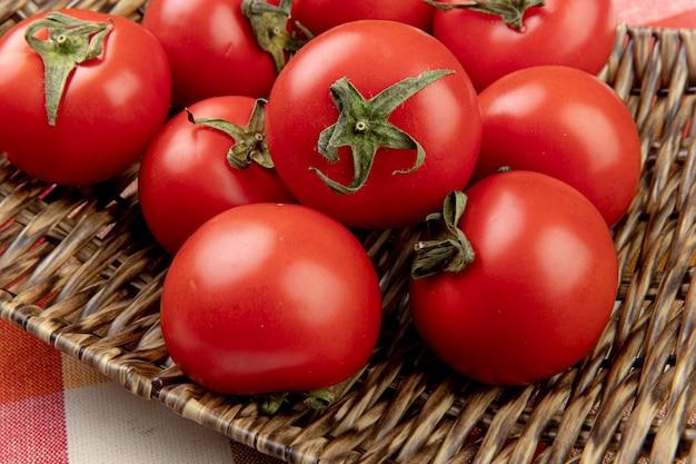 Nahaufnahme von tomaten in korbteller auf kariertem stoff