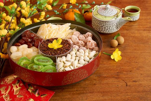 Nahaufnahme von traditionellen vietnamesischen snäcken und von nachtischen auf teller auf dem tisch