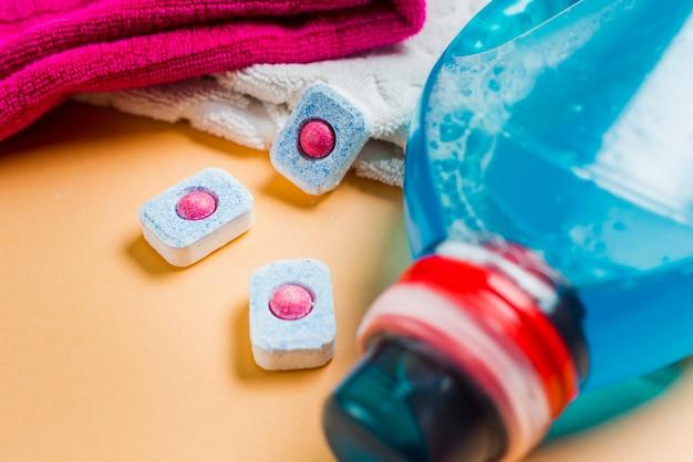 Nahaufnahme von tüchern und von flüssigem reinigungsmittel mit drei geschirrspültabletten