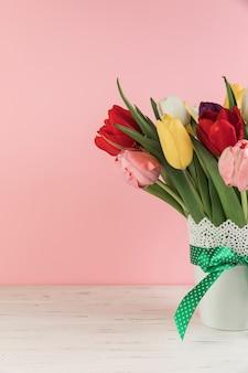 Nahaufnahme von tulpen im weißen vase mit grünem bogen auf hölzernem schreibtisch gegen rosa hintergrund