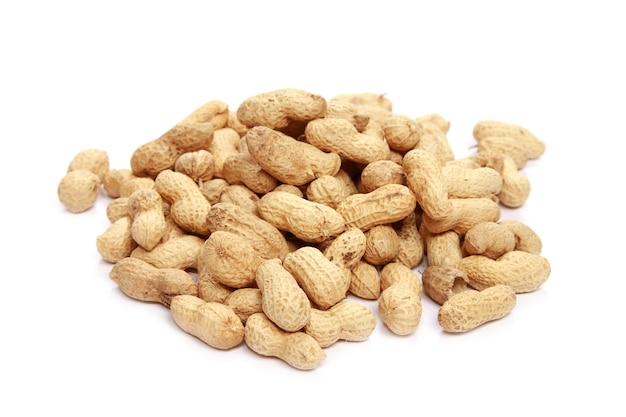 Nahaufnahme von ungeschälten erdnüssen isoliert auf weißer oberfläche