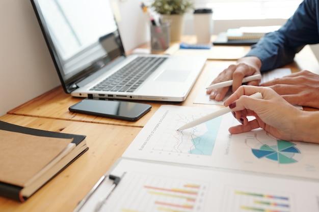 Nahaufnahme von unternehmern, die den bericht über die geschäftstätigkeit von unternehmensunterteilungen diskutieren