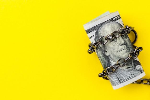 Nahaufnahme von us 100 100 dollar unter metallischer kette auf gelbem hintergrund