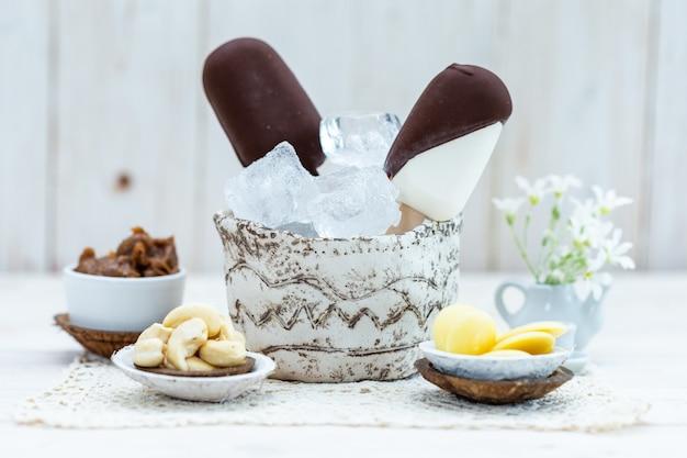Nahaufnahme von veganem eis am stiel in einer schüssel mit eiswürfeln auf einem tisch mit anderen snacks