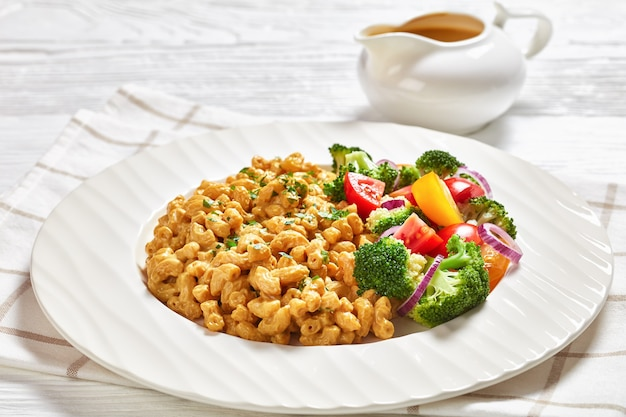 Nahaufnahme von veganem mac und käse mit nährhefesauce und gemüsesalat auf einem weißen teller auf einem weißen holztisch mit silbernem besteck, landschaftsansicht von oben