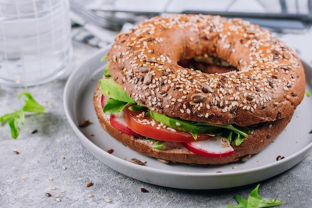 Nahaufnahme von veggie-bageln auf platte. konkrete tabellenhintergrund. gesundes mittagessen. köstliches ausgewogenes essen