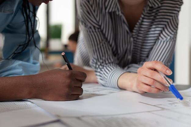 Nahaufnahme von verschiedenen architektenfrauen, die am schreibtisch an blaupausenplänen arbeiten. professionelles ingenieurteam, das das konstruktionslayout für das baumodell-maquette-projektdesign entwirft