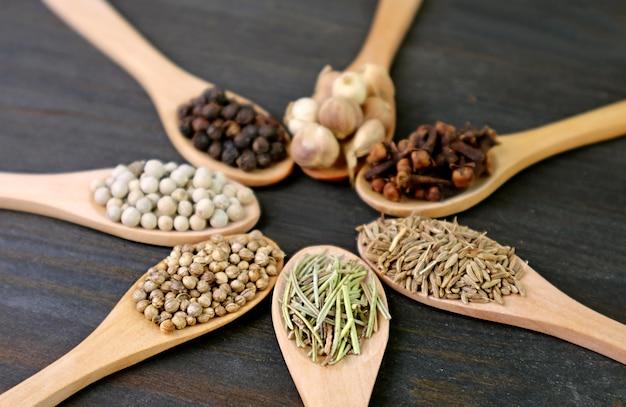 Nahaufnahme von verschiedenen aromatischen gewürzen in holzlöffeln mit selektivem fokus