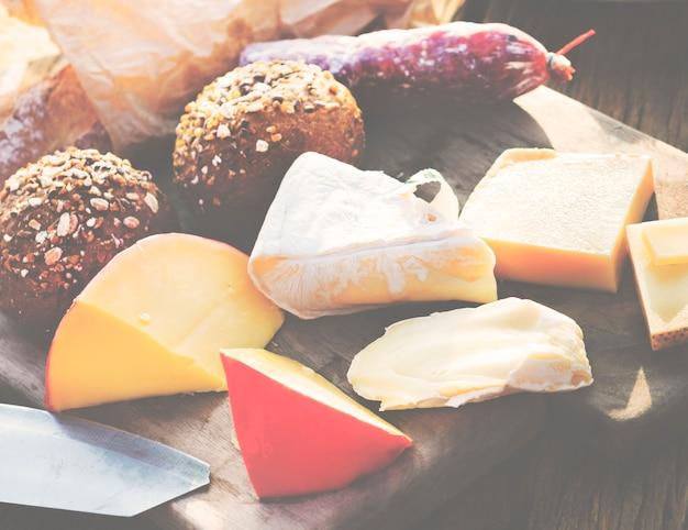 Nahaufnahme von verschiedenen käsen auf holztisch mit brötchen