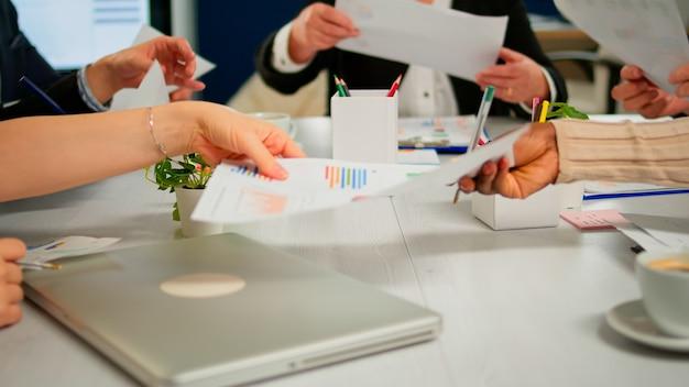 Nahaufnahme von verschiedenen startup-unternehmenskollegen, die sich am professionellen arbeitsplatz treffen, ideen über das management von finanzstrategien austauschen und austauschen. gemischtrassige geschäftsleute, die im büro zusammenarbeiten.