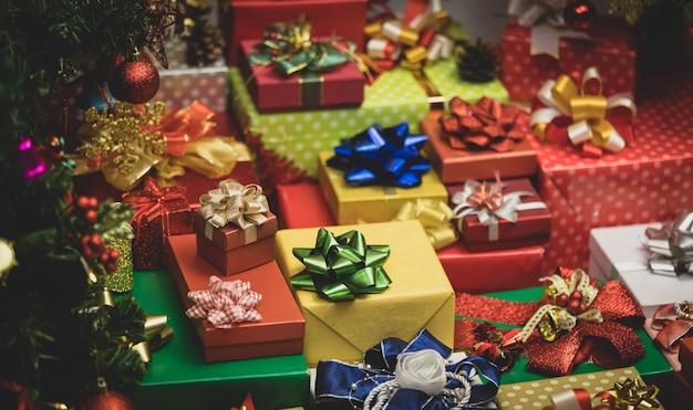 Nahaufnahme von vielen frohen weihnachtsabend verpackten geschenkboxen mit bunten bändern und schleifen mit dekoration xmas pine tree mit glänzenden kugel kugeln glocken socken eisflocken in der nähe.