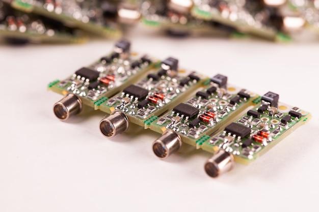 Nahaufnahme von vier kleinen mikroschaltungen pcb mit dem ausgang für den draht, der auf einem weißen tisch liegt. konzeptproduktion von lautsprechern und playern für audiogeräte.