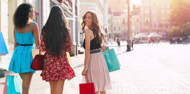 Nahaufnahme von vier mädchen, die durch die straßen der stadt gehen und einkaufstüten mit dem rücken zur kamera tragen