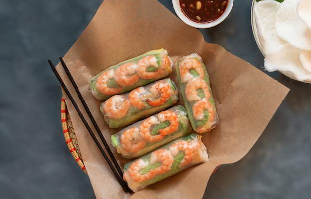 Nahaufnahme von vietnamesischen frühlingsrollen mit zarten hühnchen-tiger-garnelen-reis-chips auf grauem hintergrund sesamsauce