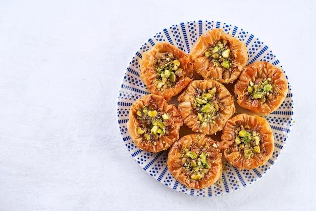 Nahaufnahme von vögelnest baklava mit pistazien auf einem leuchttisch mit platz für text. draufsicht.