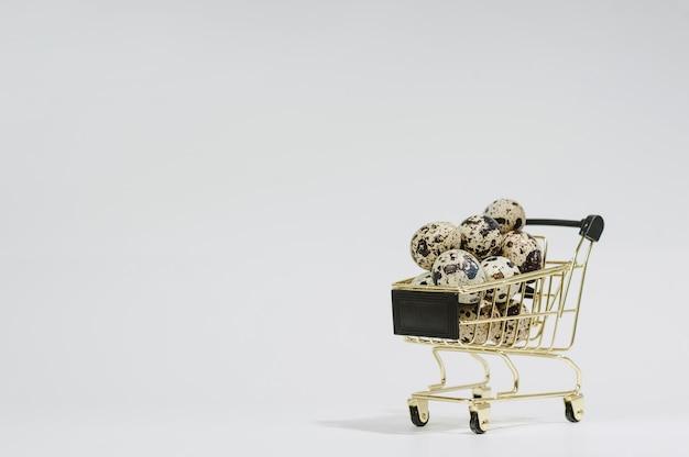 Nahaufnahme von wachteleiern in einem wagen. auf hellem hintergrund. oster- und eierverkaufskonzept.