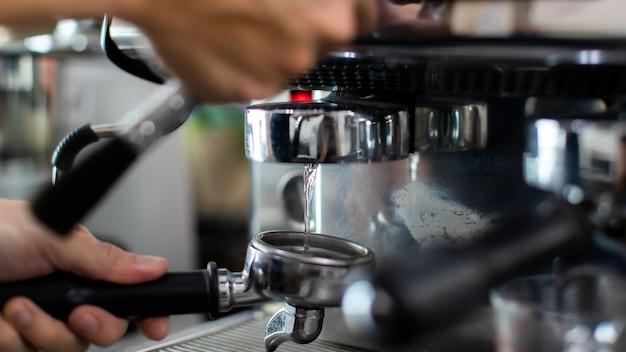 Nahaufnahme von warmem wasser beim ausgießen aus der kaffeemaschine. ein mann-barista, der sich auf das pressen von gemahlenem kaffee zum brauen von espresso oder americano in einem café vorbereitet.