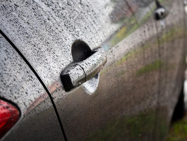 Nahaufnahme von wassertropfen auf dunkelgrauem auto nach regen.