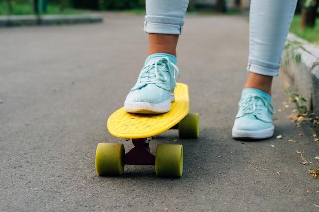Nahaufnahme von weiblichen beinen in den blue jeans und in turnschuhen, die auf einem gelben skateboard stehen