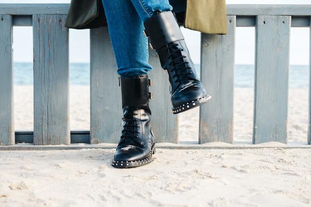Nahaufnahme von weiblichen beinen in den schwarzen stiefeln und in den jeans