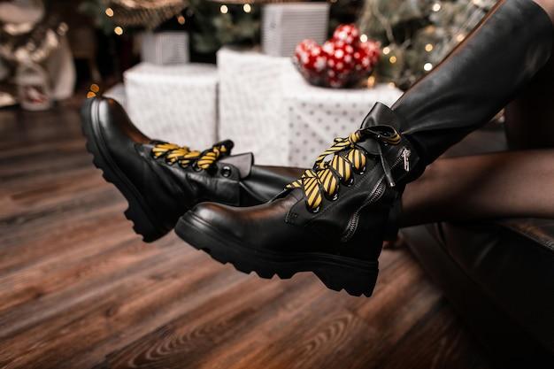 Nahaufnahme von weiblichen beinen in modischen schwarzen lederstiefeln mit gelben schnürsenkeln im studio