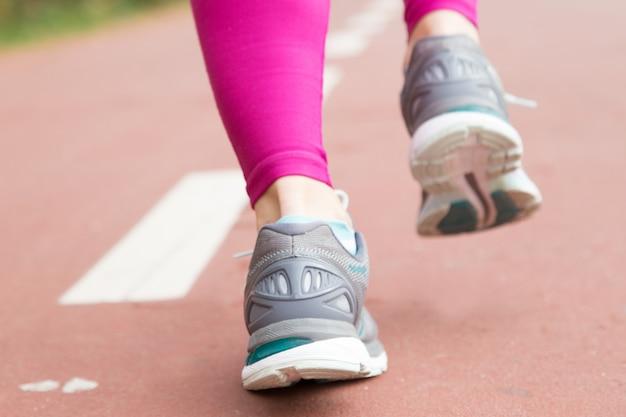 Nahaufnahme von weiblichen füßen in den sportschuhen auf stadion