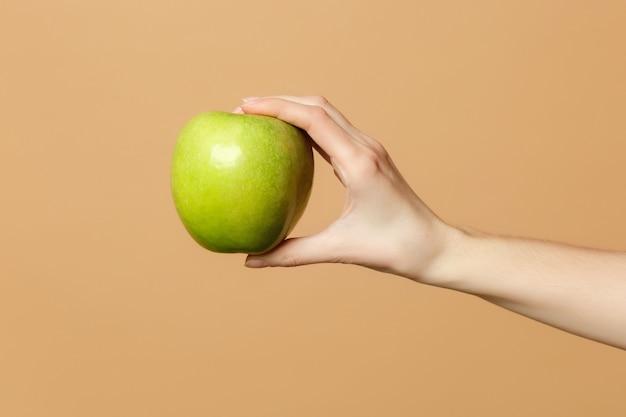 Nahaufnahme von weiblichen hält in der hand frische reife grüne apfelfrucht isoliert auf beige pastellfarbener wand