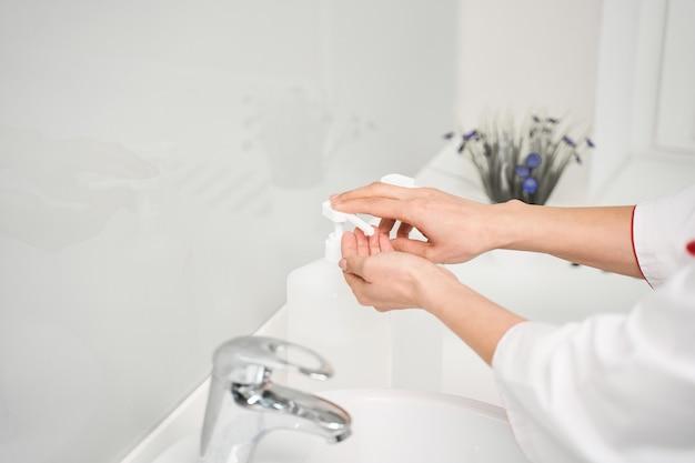 Nahaufnahme von weiblichen händen, die den knopf drücken, um flüssigseife zu erhalten, arzt, der in der nähe des waschbeckens steht