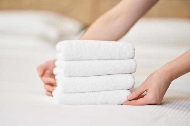 Nahaufnahme von weiblichen händen, die einen stapel frischer weißer badetücher auf das bettlaken im zimmer legen. hotelservicekonzept