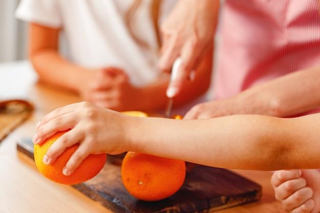 Nahaufnahme von weiblichen händen, die orange schneiden