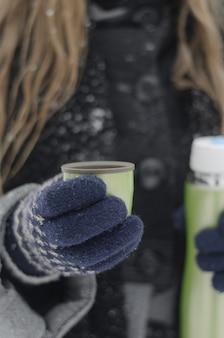 Nahaufnahme von weiblichen händen in gestrickten handschuhen, die heißen kaffee von einer thermoskanne an einem kalten winterschneetag gießen