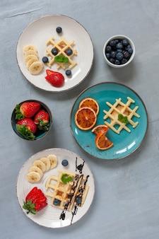 Nahaufnahme von weichen wiener waffeln auf dem teller mit blaubeeren, erdbeere und schokoladensauce