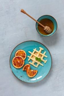 Nahaufnahme von weichen wiener waffeln auf dem teller mit blaubeeren, erdbeeren und honney
