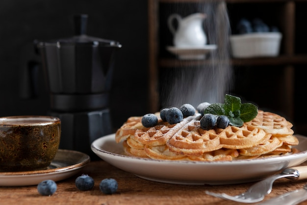 Nahaufnahme von weichen wiener waffeln mit blaubeeren, bestreut mit puderzucker, einer tasse kaffee und einer kaffeekanne