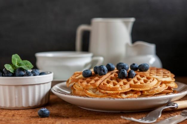 Nahaufnahme von weichen wiener waffeln mit blaubeeren, einer tasse kaffee und einer kaffeekanne