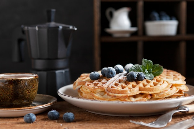 Nahaufnahme von weichen wiener waffeln mit blaubeeren, puderzucker, einer tasse kaffee und einer kaffeekanne