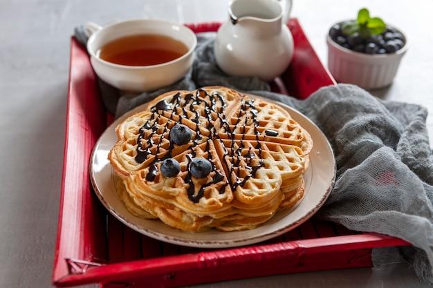 Nahaufnahme von weichen wiener waffeln mit blaubeeren, schokoladensauce und einer tasse tee