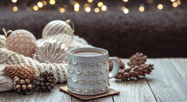 Nahaufnahme von weihnachtsbecher und festlichem dekor auf verschwommenem dunklem hintergrund mit bokeh.