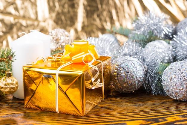 Nahaufnahme von weihnachtsgeschenk in gold auf rustikalem holztisch mit kerze und immergrünen zweigen dekoriert in silbergirlande und kugeln