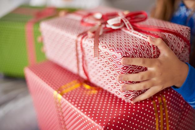 Nahaufnahme von weihnachtsgeschenken in den händen des kindes