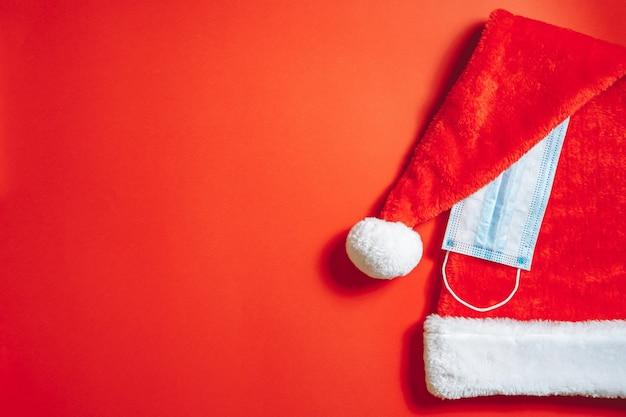 Nahaufnahme von weihnachtsweihnachtsmütze und medizinischer maske auf einem roten hintergrund. neujahrs- und pandemiekonzept.