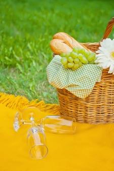 Nahaufnahme von weingläsern auf der gelben abdeckung, dem picknickkorb mit lebensmittel und der blume auf dem grünen gras