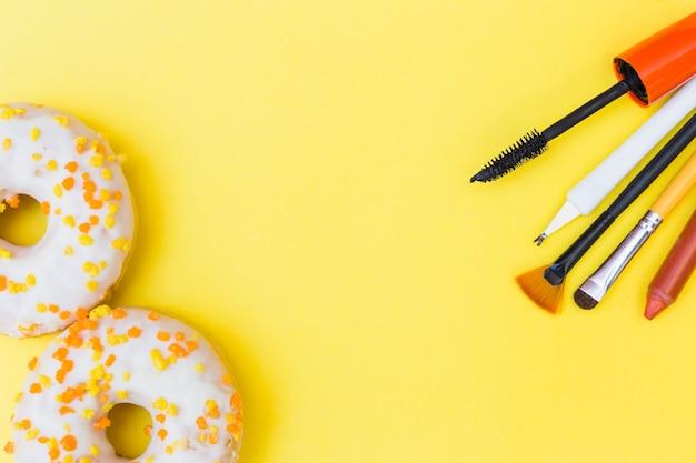 Nahaufnahme von weißen donuts mit make-up pinsel; lippenstift; wimperntusche und häutchen auf gelbem hintergrund