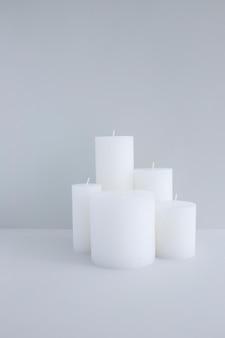 Nahaufnahme von weißen kerzen gegen grauen hintergrund