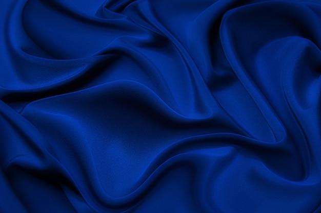 Nahaufnahme von wellen in blauem seidenstoff. satin-textilhintergrund.